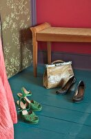 Ladies' shoes and handbag on petrol blue wooden floor, antique bedroom bench with rattan seat against wall painted deep pink