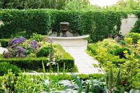 Classic gardens with urn fountain against climber-covered garden wall