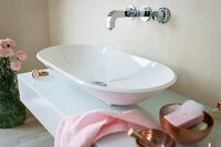 A designer console basin on a washstand with a glass surface and a wall tap