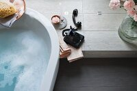 A partially visible bathtub next to an old-fashioned black telephone on a platform