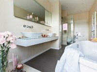 A wall console with a glass surface and two oval washing bowls with a custom-built mirror and a glass shelf above it and a shower cubicle in the background