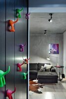 Colourful plastic hooks on black wall next to open doorway leading to living room with grey corner sofa against concrete wall