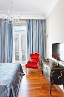 Antique-style chest of drawers, Rococo-style, red armchair and pale blue curtains at balcony windows in traditional bedroom