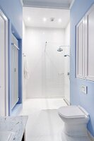 Pedestal toilet against wall painted pale blue in front of white, floor-level shower