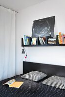Black bookshelf above double bed with black and white patterned textiles in bedroom