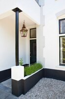 Front porch of traditional Dutch house with steel pillar, integrated planter and retro lantern