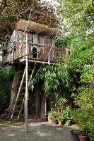 Enchanting tree house made from weathered wooden boards with plexiglas porch in garden