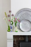 Pewter plates and collection of small vases containing a few flowers on mantelpiece