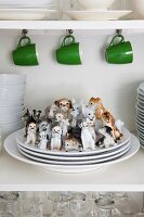 Green coffee mugs hanging from row of hooks and china dogs on stack of plates in kitchen cabinet