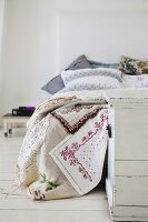 Lacy patchwork blanket and white vintage trunk at foot of bed