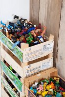Colourful toys in stacked fruit crates against board wall