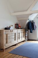 Rustic, plain wood sideboard in attic room; clothing hung from metal rod and stacked suitcases in background