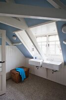Attic bathroom with lavender-blue walls, white wainscoting and twin sinks below wide dormer window