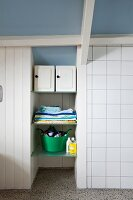 Repurposed storage cabinets on glass shelves in niche in attic bathroom