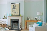 Open fireplace and white armchair in front of family photos on artistic console table against pastel wall in elegant interior