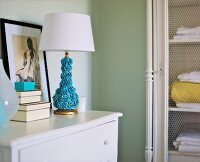 Artistic, turquoise table lamp with floral base on white chest of drawers next to set of boxes and nude drawing in vintage interior