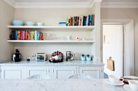 View across marble table top to fitted sideboard in niche below books and ornaments on two white, floating shelves in vintage ambiance