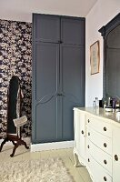 Bedroom with white dressing table and black fitted wardrobe against floral wallpaper