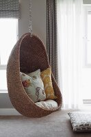 Comfortable wicker hanging chair in interior with walls painted pale grey