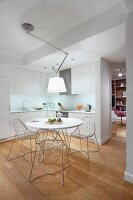 Wire chairs at white, round dining table below anglepoise ceiling lamp in open-plan fitted kitchen