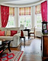 Living room with bay window, striped Roman blinds and pink curtains on lattice windows; couch and antique side table in foreground
