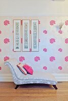 Elegant chaise longue with pale, patterned upholstery against wallpaper with pattern of pink flowers on pale background