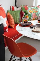 Orange, classic chair at marble-topped table and scatter cushions arranged on bench to one side