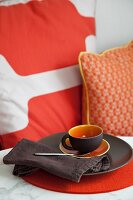 Brown and orange place setting with cup