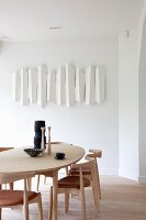 Modern dining area with pale wooden chairs and table and white artwork on wall