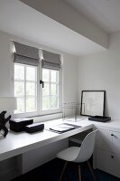 Workspace with white, classic shell chair and fitted desk below window
