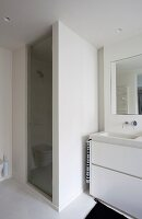 Detail of washstand with white base unit next to shower cubicle with masonry wall and glass door