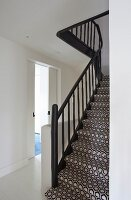 Staircase with black balustrade and black and white, geometric carpet in stairwell