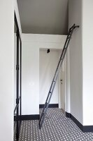 White installation in hallway, ladder attached to wall and retro carpet with black and white geometric patter
