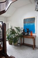 Stairwell with pale grey, mosaic floor tiles, antique console table and potted palms below modern artwork on wall