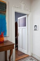 Open interior door with glass panel, floral stucco elements above door frame and console table to one side
