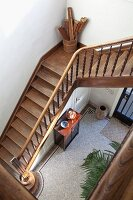 View down stairwell with wooden staircase, turned balusters to foyer in traditional interior