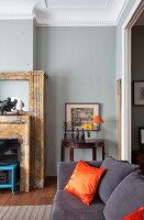 Dark grey couch with orange, silk scatter cushions in traditional living room with grey-painted wall
