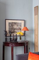 Sculptures and delicate table lamp on antique, semicircular console table against pale grey wall