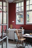 View through open lattice doors of wooden armchair with high backrest at dining table in simple kitchen with walls painted Bordeaux red