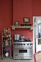 Stainless steel gas cooker against Bordeaux-red wall with masonry extractor hood in traditional kitchen