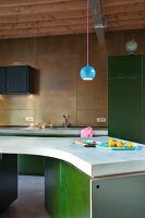 Spherical, blue lamp above curved island counter with green base units; back wall of kitchen clad in brass panels