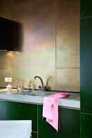 DIY kitchen counter with green cabinets, concrete worksurface and back wall clad in brass panels