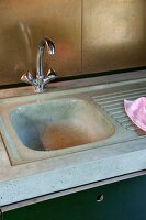 Moulded concrete kitchen worksurface and sink with recycled brass panels used as innovative splashback