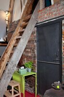 Wooden ladder leading to gallery level in loft-apartment kitchen; brick wall with industrial, black metal door