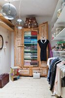 Dressing room with women's clothing on clothes rack below shelves and old wooden wardrobe in background
