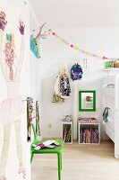 Painted interior door, green chair and shelving modules on wooden floor in child's bedroom