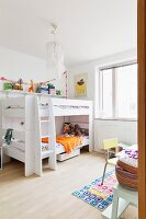 White bunk beds with ladder next to window in corner of children's bedroom; chair and section of table in foreground