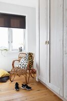Retro-style cane armchair in corner below window next to white-painted wooden wardrobes