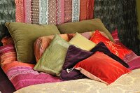 Scatter cushions on bed with brocade bedspread, wall decorated with mink furs, velvet and silk fabrics with sequins