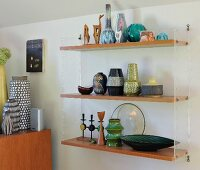 Collection of retro vases on wooden shelves supported by transparent plastic end panels
